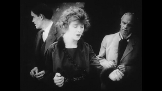 1910s: Woman faints while talking, man behind her looks stunned. Another man enters the room and everyone flees. Young woman regains consciousness and everyone looks relived.
