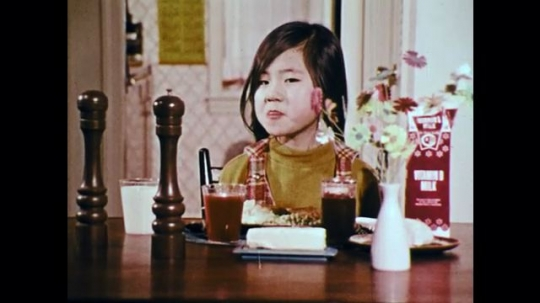 1970s: UNITED STATES: girl with food. Cartoon frog. Man looks at book. Milk group title. Cartoon frogs in band. Meat group title. Fruit and vegetable group title. Bread and cereal title.
