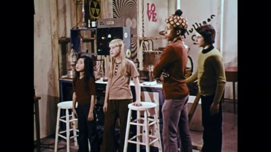 1970s: UNITED STATES: children stand and listen. Man speaks to boy. Man looks worried.