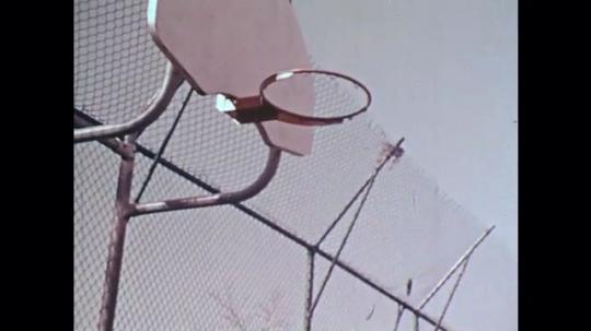 1970s: UNITED STATES: children play basketball. Children play leap frog in park. Children run along path