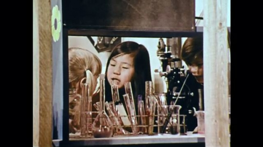 1970s: UNITED STATES: children do science tests at home. Child puts food on microscope slide.
