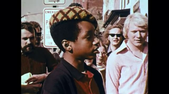 1970s: UNITED STATES: boy speaks to general public in street interview. Lady speaks to boy with microphone. Man speaks.