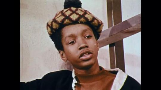 1970s: UNITED STATES: boy speaks. Boy knocks on wall. Children gather on stairs