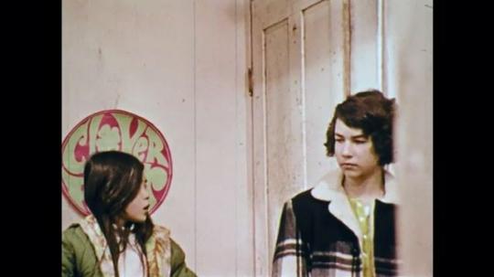 1970s: UNITED STATES: man bangs on door. Boy lets man in through door. Man speaks to children on stairs