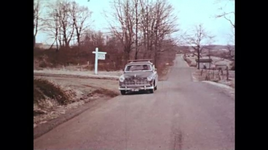 1970s: UNITED STATES: front view of car on road. Car stops on road. Children run across ground.