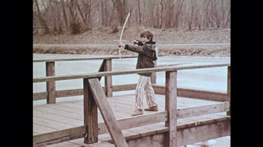 1970s: UNITED STATES: boy prepares to fire arrow. Boy fires arrow. Boy hits target, Boy speaks to camera