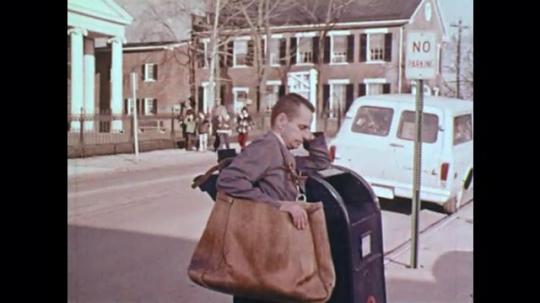 1970s: UNITED STATES: mail man sleeps on mail box. Lady sleeps in car. Gas station attendant sleeps. Children look through school window