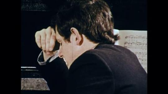 1970s: UNITED STATES: teacher sleeps in class. Girl speaks. Students sleep in classroom