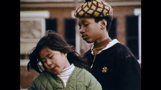 1970s: UNITED STATES: boy and girl on park bench. Man speaks. Man and children sit on park bench and talk.