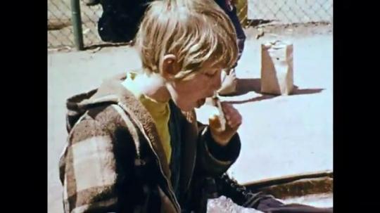 1970s: UNITED STATES: boy eats sandwich. Children run from school. Man dances. Children play in band on steps.