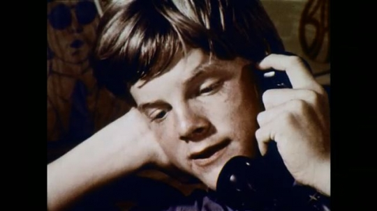 1970s: UNITED STATES: boy speaks on telephone. Boy with dirty feet. Close up of toes