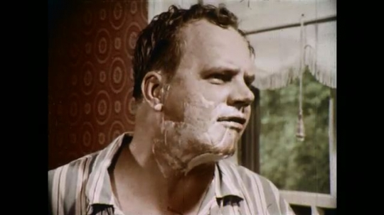 1970s: UNITED STATES: man looks in mirror and shaves face. Man speaks.