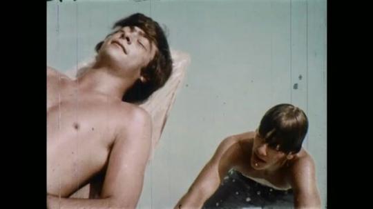 1970s: UNITED STATES: boy in swimming pool. Boy sunbathes in pool. Boy looks at friend. Boy talks