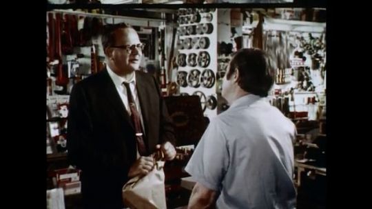 1970s: UNITED STATES: shop assistant talks to customer in shop. Man listens. Man gives advice. Man shakes head.