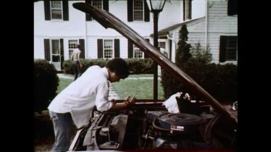 1970s: UNITED STATES: man runs across garden. Boy cuts hand on car. Boy feels faint.