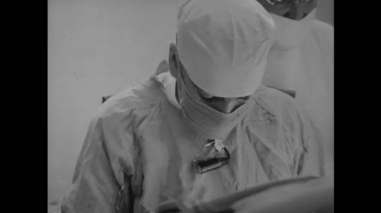 1950s: Doctor in scrubs and mask looks down. Two men, including one in a white jacket, look down and converse. Doctors speak.