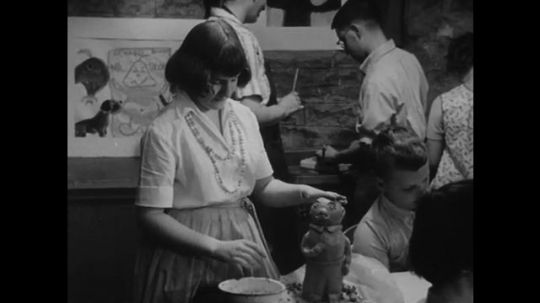 1950s: Girl adjusts head of clay figure, uses tool to smooth clay. Boys talk. Boy paints. Sign says Apothecary: Prescriptions Filled. Cartoon drugstore. Cartoon pharmacist on ladder looks at jars.