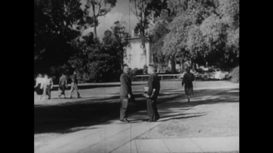 1950s: UNITED STATES: men stop during park walk. Men shake hands. Men speak