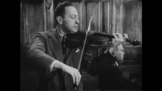1950s: UNITED STATES: man plays piece on violin