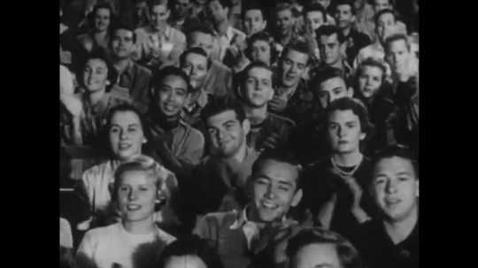 1950s: UNITED STATES: audience claps. Man strikes violin with fingers. Man plays violin