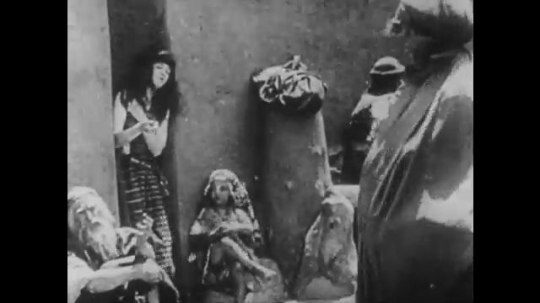 1910s: UNITED STATES: child knits in street. People in street. Lady looks through window. Women work