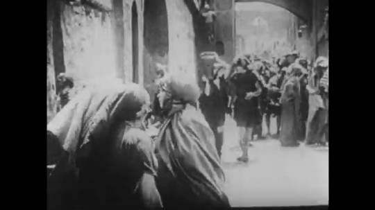 1910s: UNITED STATES: women carry water through village street. Ladies greet each other in street. Lady carries baby.