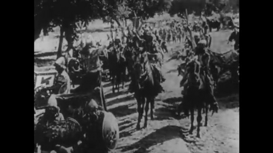 1910s: UNITED STATES: men on horses charge along track in dust. Man stands in chariot. Horses rush across field