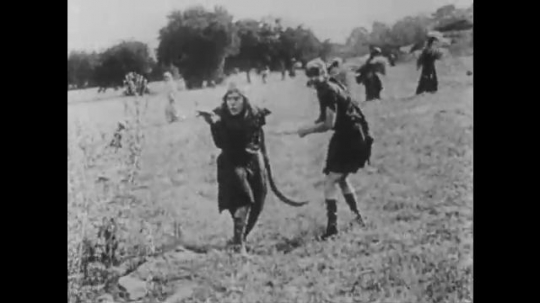 1910s: UNITED STATES: men in field. Woman hides behind well. Men fight outside gates