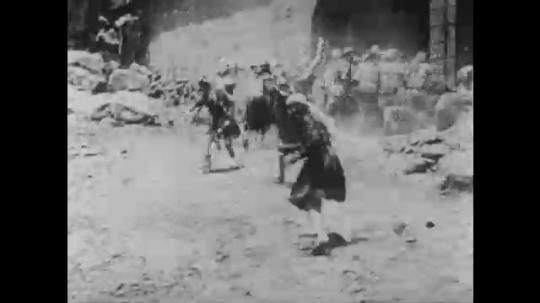 1910s: UNITED STATES: ladies run from invaders. Men run through gates with swords. Soldiers fight. Man waves arms in street
