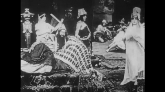 1910s: UNITED STATES: lady dances in street for man. Man plays music for leader on throne.