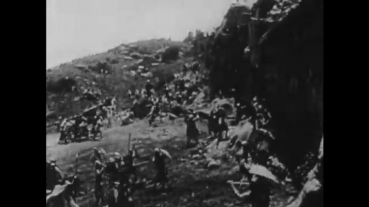 1910s: UNITED STATES: men attack city walls. Soldiers fight in street. Soldiers run