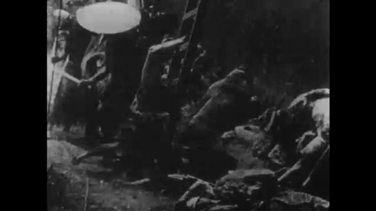 1910s: UNITED STATES: soldier falls on ladder. Ladies pray in tower. Soldiers bang gate with wood. Soldiers fight by city walls