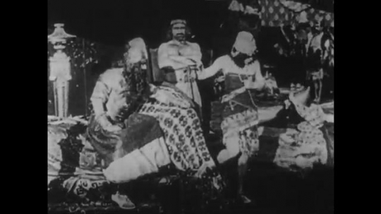 1910s: UNITED STATES: man sits on throne. Man attacks servant. People fight on city walls