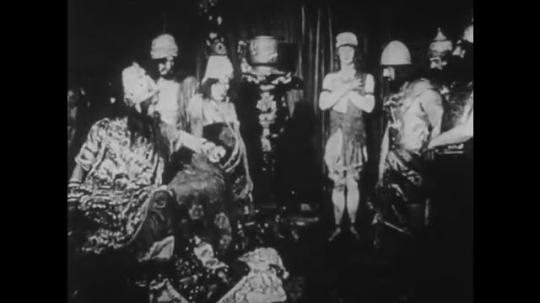 1910s: UNITED STATES: men stand around leader on throne. Lady walks to window.