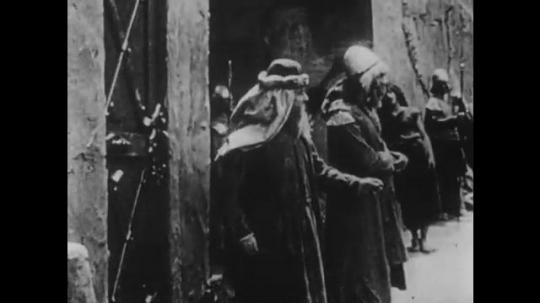 1910s: UNITED STATES: men stand in street. Man with sword bangs on gate. Man waves at door. Ladies leave through door