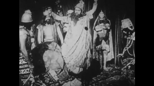 1910s: UNITED STATES: men bow around leader. Men in woods. Lady speaks to men in woods. Lady dances for man
