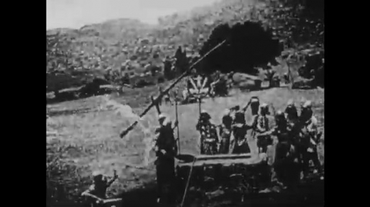 1910s: UNITED STATES: people at well. Soldiers stand by city walls with swords and shields. Women beg soldiers with open arms
