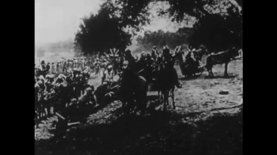 1910s: UNITED STATES: soldiers wait in grounds. Soldiers on horseback. Men ride horses. Men on chariots. Men fight with swords