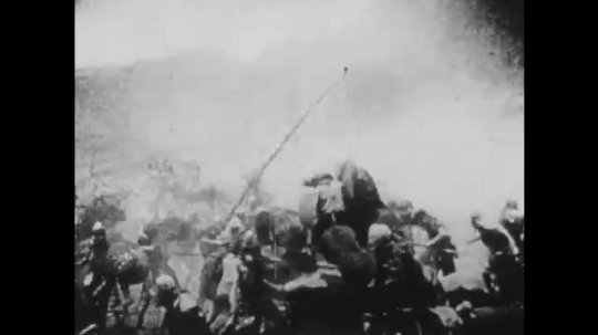 1910s: UNITED STATES: men in battle by well. Men on horses. Soldiers fight with swords. Soldiers rush across field