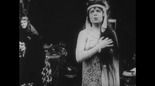 1910s: UNITED STATES: lady holds hand across her chest. Lady wraps cloak around girl. Man on throne