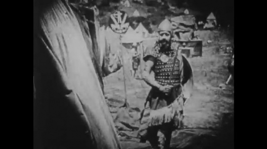 1910s: UNITED STATES: guard stands outside tent. Goblet falls. Lady stands by body. Lady in cloak outside tent. Lady drops sword. Lady gets scared. Lady stands outside tent