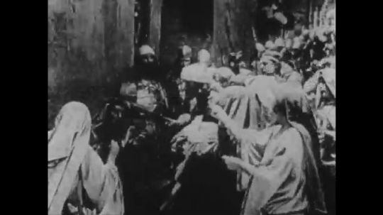 1910s: UNITED STATES: women speak with soldiers by city walls. Man gets annoyed. Ladies bow