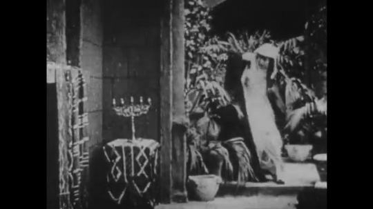 1910s: UNITED STATES: lady rushes to window. Man raises head of dead leader. Lady looks horrified. Soldiers rush through gates. Men with horses stand outside gate