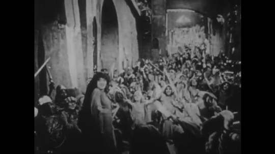 1910s: UNITED STATES: people clap and celebrate Judith in street. People cheer inside city walls