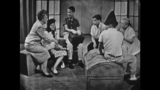 1950s: UNITED STATES: teacher talks with students. Children role player different characters in circle