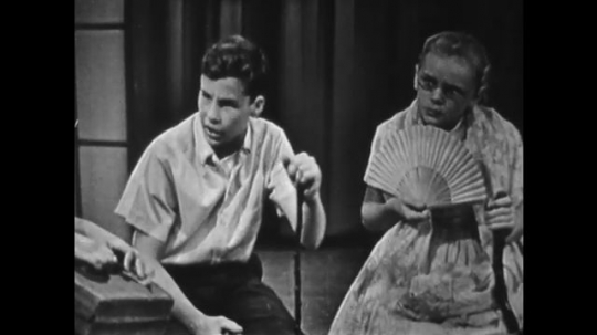 1950s: UNITED STATES: boy with stick speaks in character. Girl plays part of lady with fan