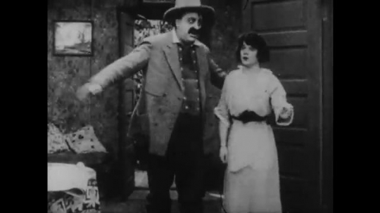 1910s: man with cowboy hat talks to woman, points around living room, walks to doorway and blows a kiss. man with mustache straightens clothes and sits down in chair. woman closes door.