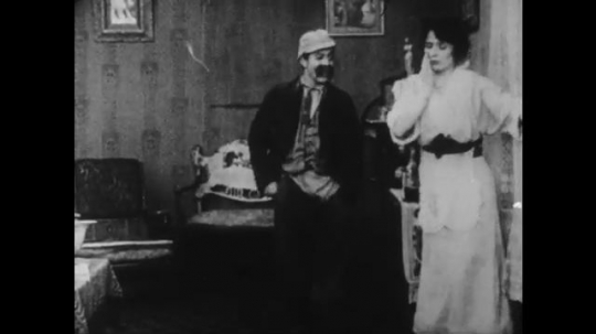 1910s: man with mustache grabs and clutches waist of woman who fights back and bites his hand as anger grows.