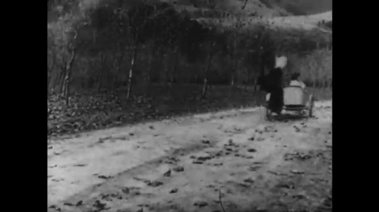 1910s: man with mustache wildly steers motorcycle and restrains woman in sidecar. man with cowboy hat rides horse and fires gun. three men in police uniforms run down dirt road.