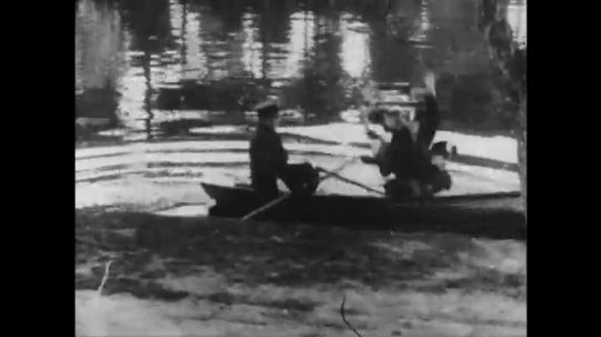 1910s: men sloppily row boat on water. man with cowboy hat on horse chases man with mustache on motorcycle with woman in sidecar across bridge. man ties up pony, pulls out rope and runs.